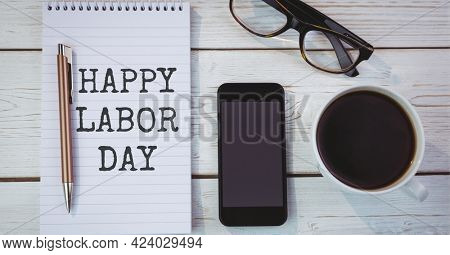 Happy labor day text over diary against coffee cup, glasses and smartphone on wooden background. american labor day template background design concept