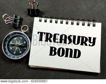 Finance Concept.text Treasury Bond On Notebook With Paper Clips And Compass On Black Background.