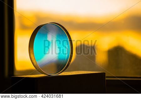 Transparent Round Turquoise Glass Sphere With Blue Reflection On A Bright Yellow Light Back Of The C
