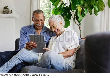 Elderly couple using a tablet on a couch
