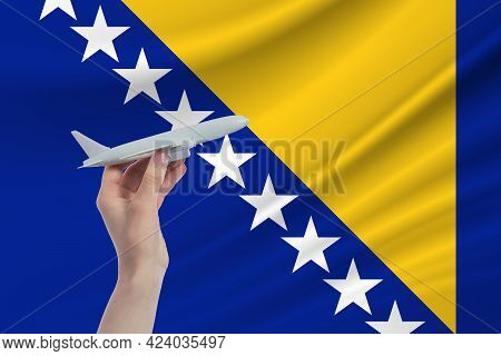 Airplane In Hand With National Flag Of Bosnia And Herzegovina. Travel To Bosnia And Herzegovina.