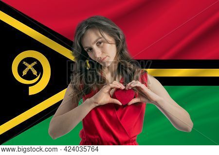 Love Vanuatu. A Girl Holds A Heart On Her Chest In Her Hands Against The Background Of The Flag Of V
