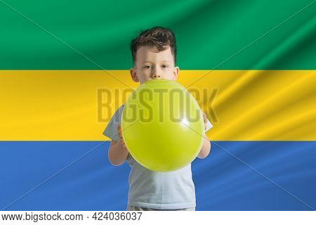 Children's Day In Gabon. White Boy With A Balloon On The Background Of The Flag Of Gabon. Childrens