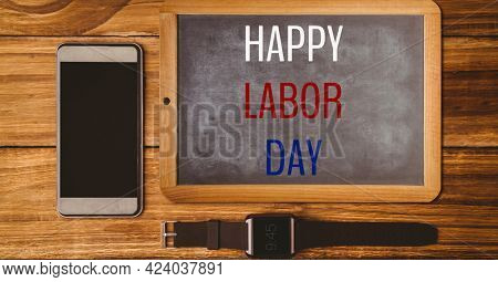 Happy labor day text over wooden slate, smartphone and watch on wooden background. american labor day template background design concept