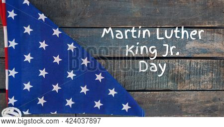 Martin luther king jr day text and folded american flag on wooden background. martin luther king jr day template background design concept
