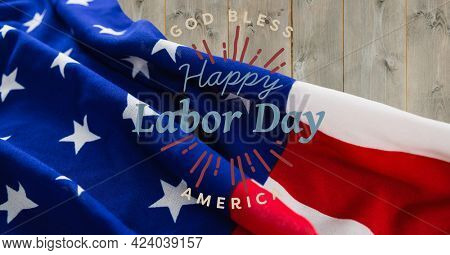 Happy labor day text against american flag on wooden background. american labor day template background design concept