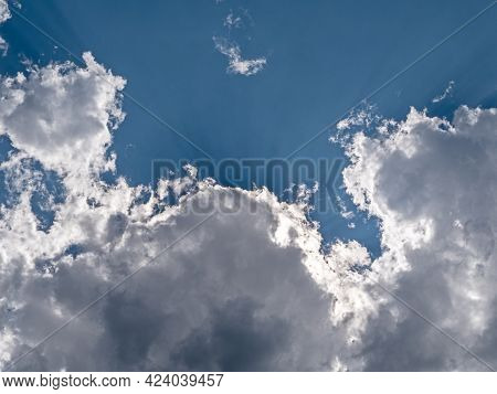 Sunrays Shining Through White Clouds On Blue Sky Background