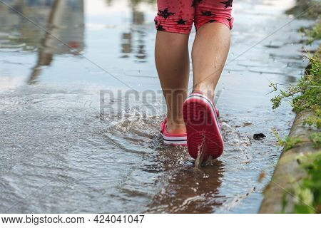 Children's Feet Walking In A Muddy Puddle After The Rain.