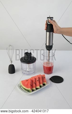 Whisking Watermelon In A Bowl With Immersion Hand Blender. Electric Kitchen Appliances For Making Ju