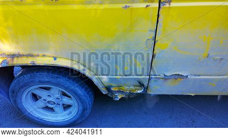 Sheet Metal Corrosion Over Wheel Of Old Yellow Car. Rusty Messy Surface. Damaged Grunge Dirty Textur