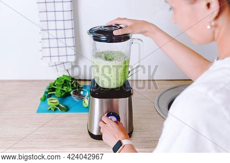 Woman Is Making Homemade Healthy Smoothie. Vegetarian Green Cocktail From Spinach, Broccoli And Coco