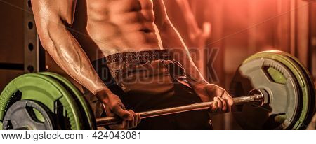 Athletic Man With Six Pack, Perfect Abs. Sporty Man Lifts Barbell In Gym. Closeup Deadlift Barbells