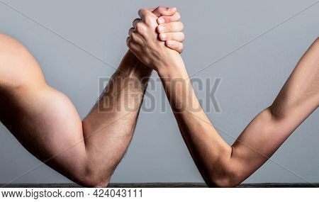Arm Wrestling. Heavily Muscled Man Arm Wrestling A Puny Weak Man. Arm Wrestling Thin Hand And A Big