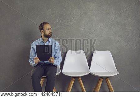 Young Man Sitting On Chair, Holding Resume And Looking Away Waiting For Job Interview