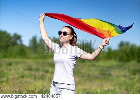 Portrait Of Young Lesbian Woman In Sunglasses, Beautiful Girl Is Waving Rainbow Lgbt Color Gay Flag