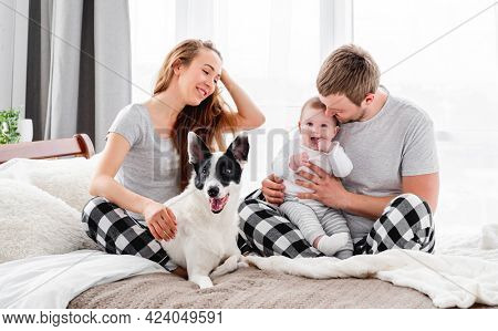 Beautiful family with baby boy sitting on the bed with cute dog and smiling. Mother and father with their son and doggy togetherin the morning. Beautiful parenthood time. Pet with owners