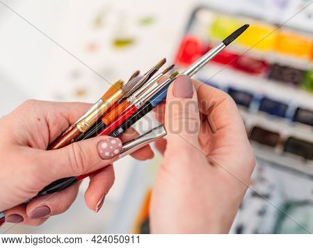 Artist hands with different size and colors paintbrushes closeup view with watercolor on background
