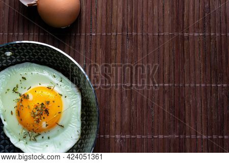 Frying Pan With Fried Egg On A Bamboo Table.