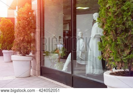 Mannequins In Fashion Shop Display Window. Female Casual Style. Summer Day Sunshine. View From Stree