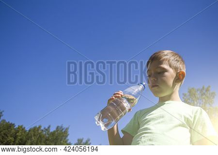 Little Boy 6-7 Years Drinking Pure Clear Water From Plastic Bottle  Against Blue Sky. Thirsty Kid On