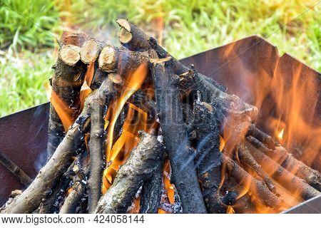 Bonfire Made Of Branches Of Fruit Trees. Flame Flutters In Wind. Green Grass Shines Through The Flam