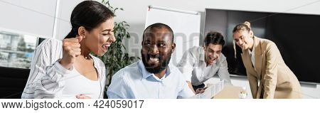 Excited African American Businesswoman Showing Triumph Gesture Near Smiling Colleagues, Banner