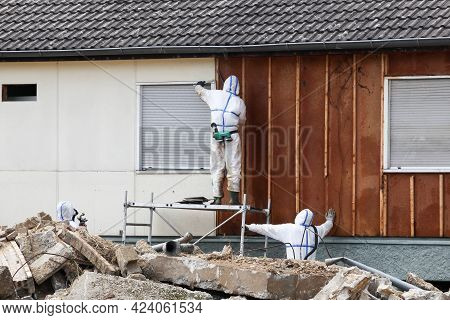 Professionals In Protective Suits Remove Asbestos On A Wall