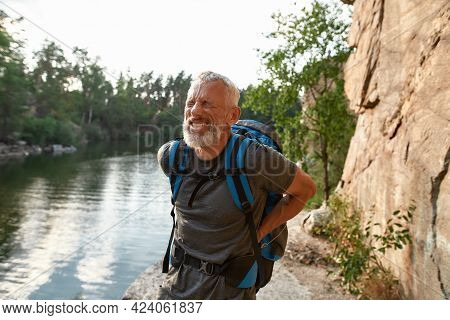 Back Hurting Middle Aged Caucasian Man During Trekking Alone In Summer Nature. Hiking, Travel Outdoo