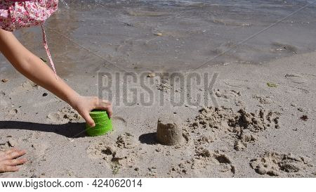 Toddler Plays With Sand Molding Toys On Wet Beach Sand By Sea. Kid Makes Sand Mold. Summer Vacation