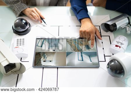 Person Watching Footage On Digital Tablet With Security Equipment On Blueprint