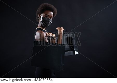 African-american Woman In Black Medical Face Mask Holds Black Shopping Bags. Safety On Black Friday
