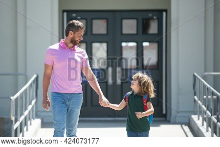Parent Taking Child To School. Pupil Of Primary School Go Study With Backpack Outdoors. Father And S