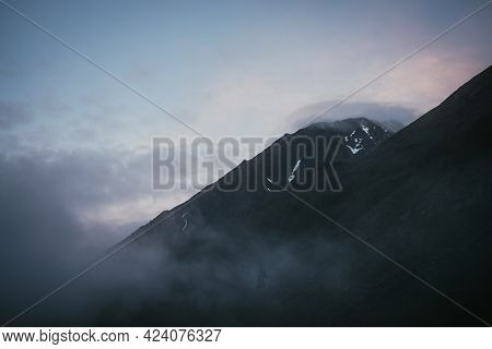 Atmospheric Alpine Landscape With Dark Mountain Silhouette Among Low Clouds Under Sunset Cloudy Sky.