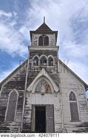 An Old Neglected White Country Church Is In The First Stages Of Disrepair.