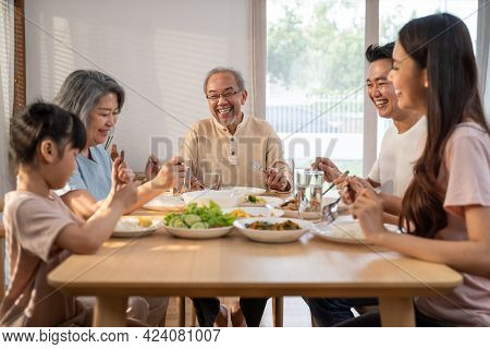 Big Asian Happy Family Spend Time Having Lunch On Dinner Table Together. Little Kid Daughter Enjoy E