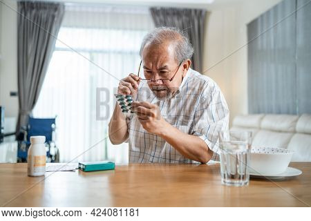 Asian Senior Elderly Male Patient On Eating Table At Nursing Home Care. Mature Older Man Wear Eyegla