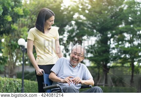 Asian Happy Senior Retired Grandfather Enjoy Outdoor At Green Park. Attractive Girl Daughter Pushing