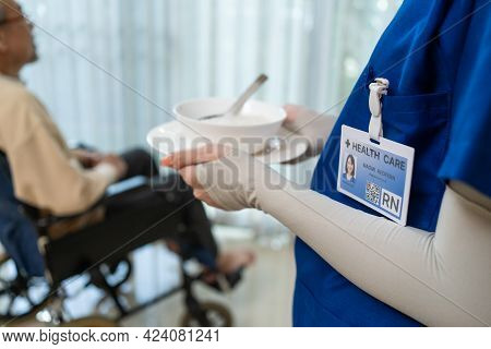 Close Up Hands Of Woman Nurse At Nursing Home Taking Care Of Disabled Senior Elderly Man On Wheelcha