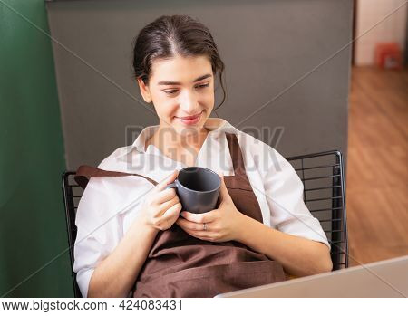 Beautiful Caucasian Barista Woman Holds Hot Coffee Cup In Coffee Break While Using Laptop At Coffee