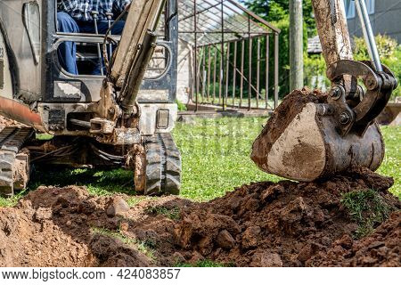 Mini Excavator With Excavated Pile Of Earth. Garden Improvement And Landscaping