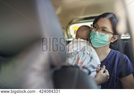Asian Young Mother Wearing Protective Face Mask Holding Adorable Newborn Little Baby Boy Sitting In
