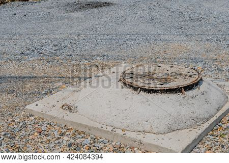 Manhole In Graded Unpaved Road In Rural Countryside.