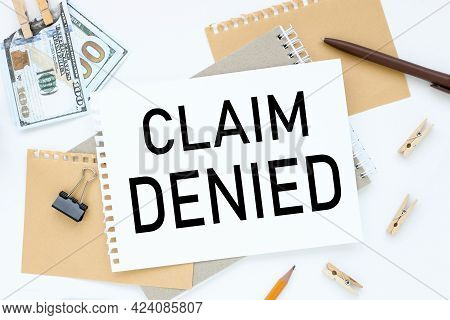 Claim Denied. Text On White Notepad Paper. On A White Photo With Torn Paper