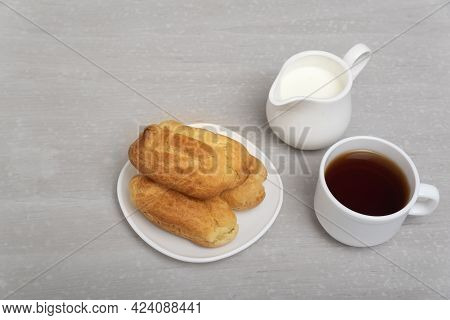 Homemade Eclairs, Coffee And Milk. Traditional French Eclairs. Profiteroles On Saucer. Gray Backgrou