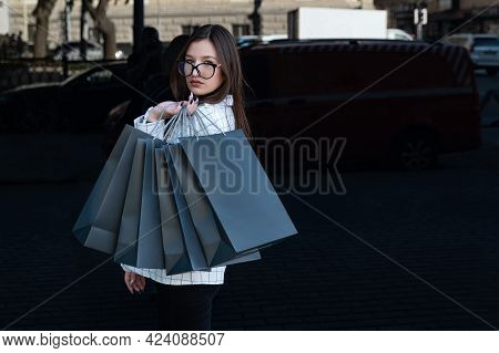 Beautiful Girl With Black Shopping Bags In Hand. Store On The Background. Black Friday, Sale, Discou