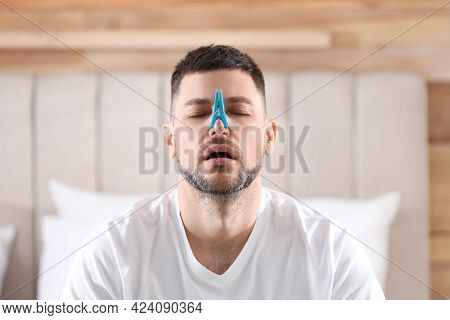 Man With Clothespin Suffering From Runny Nose In Bedroom