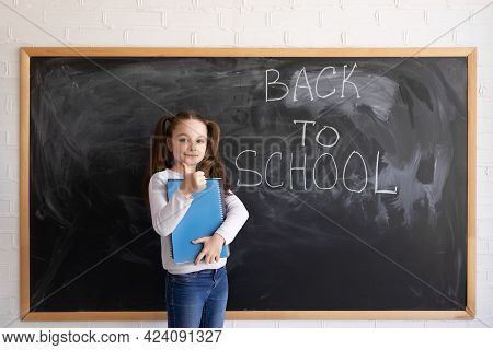 A Young Caucasian Girl Schoolgirl Stands Against The Background Of A Chalk Board. The Words Are Writ
