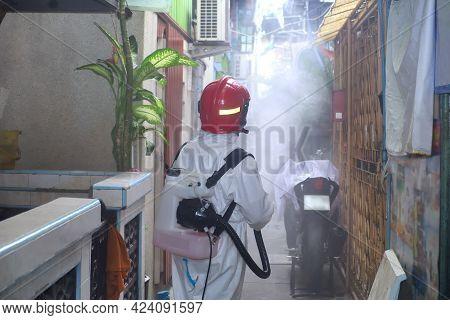 Health Worker On Ppe Suit Uniform Protector Working Sprayed Chemical Solution Disinfectants In Villa