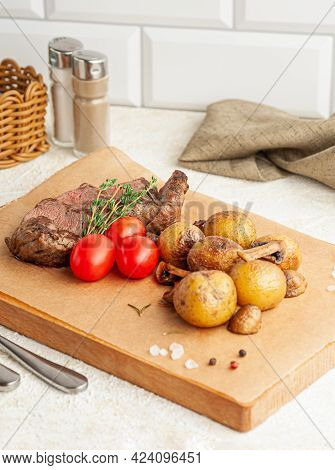 Veal Steak With Baked Potatoes And Mushrooms. Decorated With Herbs And Cherry Tomatoes. Served On A