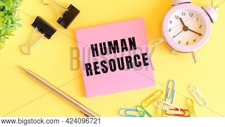Pink Paper With The Text Human Resource. Clock, Pen On A Yellow Background. Design Concept.
